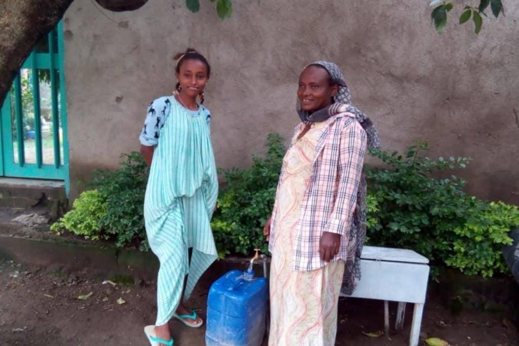 Gadisa Hurisa met haar dochter Bilusema Getachew tappen water uit de kraan bij hun huis in Adama, DebeSoloke kebele, Soloko Kurfa village. Juli 2020.